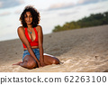 Dark-skinned girlfriend sitting on the beach in the evening 62263100