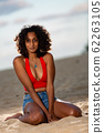 Dark-skinned girlfriend sitting on the beach in the evening 62263105