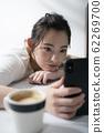 躺在桌子上同時操作智能手機的女人 62269700