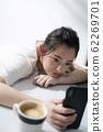 躺在桌子上同時操作智能手機的女人 62269701