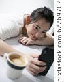 躺在桌子上同時操作智能手機的女人 62269702