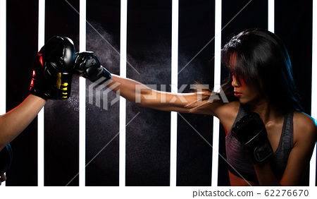 Girl exercises in Modern Neon Boxing Gym heavily 62276670
