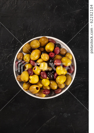 Olives assortment, overhead shot. Black, green and red olives on a dark background with a place for text 62282184