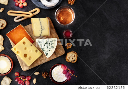 Cheese platter, shot from the top on a black background with copy space. Blue cheese, Brie, Dutch cheese and others with wine 62282186