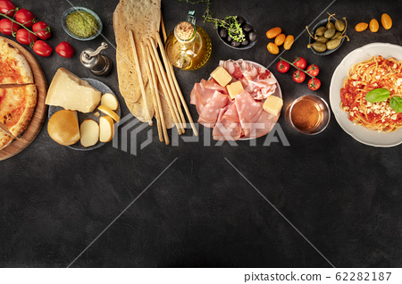 Italian food with a place for text, a flat lay design template for a restaurant. Pizza, pasta, cheese, ham, wine, olives, pesto, capers, olive oil, tomatoes, shot from the top 62282187