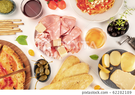 Italian food, flat lay overhead shot. Pizza, pasta, cheese, ham, wine, olives, pesto, shot from above on a white background 62282189