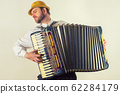 Portrait of a man in straw hat playing on 62284179