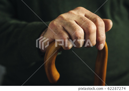 Hand of an old man highlighted in darkness 62287274