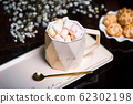 Hot chocolate with marshmallows and cookies served 62302198
