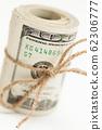 Roll of One Hundred Dollar Bills Tied in Burlap String 62306777