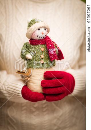 Woman Wearing Seasonal Red Mittens Holding Christmas Snowman Figurine 62307062