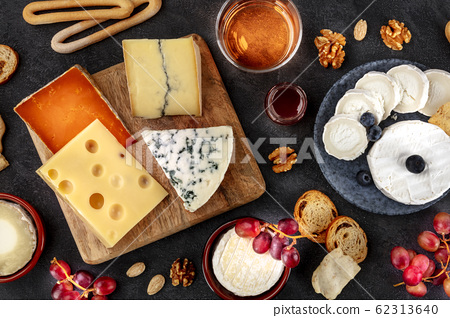 Cheese platter flat lay. Blue cheese, goat cheese, Brie, Emmental and others with wine, grapes and nuts 62313640