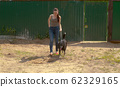 Woman volunteer walking with a dog 62329165