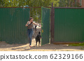 Woman volunteer walking with a dog 62329166