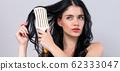 Beautiful young woman holding a hairbrush 62333047