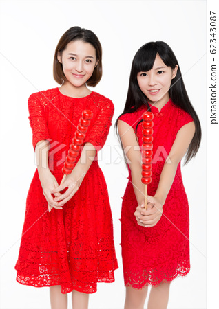 cheerful women eating Tanghulu(chinese street 62343087