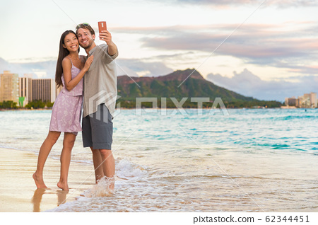 Couple walking on beach at sunset taking selfie picture on mobile phone relaxing together on Waikiki beach, Honolulu, Hawaii travel vacation. Romantic holiday destination for honeymoon 62344451