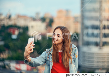 Teen girl on cityscape background making self portrait with her smart phone 62347207