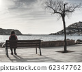 Woman hiker sit on wooden bench in port 62347762