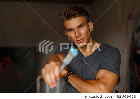 Young handsome man artist with brush in hand 62349459