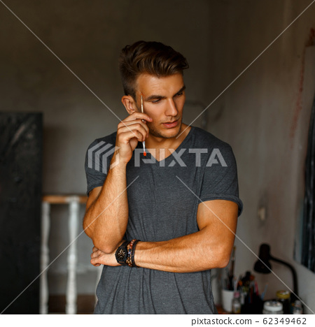 Young handsome man with a brush in a gray T-shirt 62349462