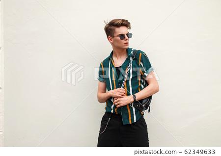 Beautiful stylish young man with sunglasses 62349633
