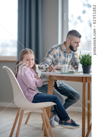 Sad little daughter and young busy dad. 62351862