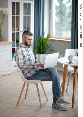Young man working on a netbook near the table. 62351925