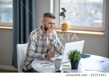 Young man in a plaid shirt sitting looking at a laptop. 62351941