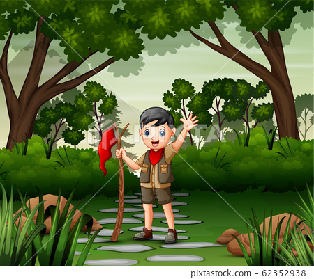 A boy scout holding a flag walking in forest 62352938