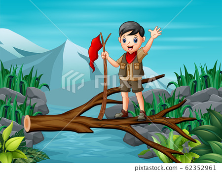 A scout boy standing at the trunk above the river 62352961