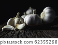Fresh white garlic on wooden table with black 62355298