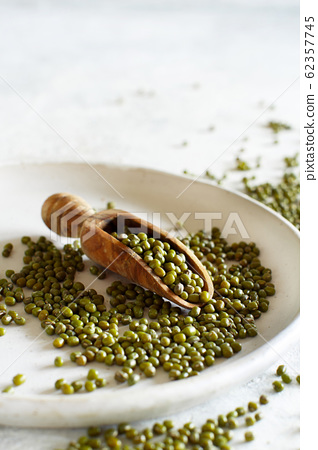 Dried mung beans with a spoon on a plate 62357745