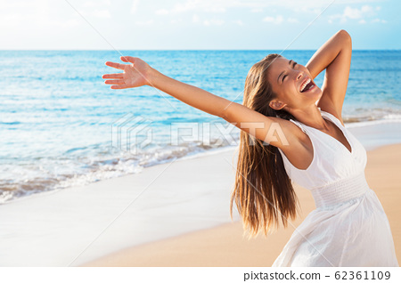 Freedom woman on beach enjoying life with open arms feeling free bliss and success on beach. Happiness Asian girl in white summer dress enjoying ocean nature sunset during travel holidays vacation 62361109