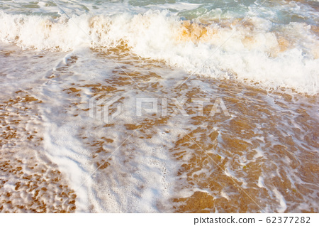 sea waves splash foam on the sunny beach 62377282