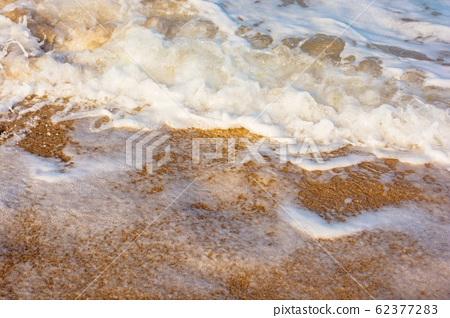 sea waves splash foam on the sunny beach 62377283