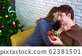 Happy lovely Caucasian couple exchange gifts on Christmas day 62381501