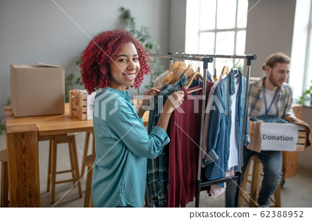 Young girl near rack with clothes man with donation box. 62388952