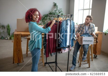 Young girl standing with clothes man sitting with charity box. 62388953