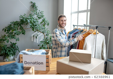 Young man standing at a rack with clothes. 62388961