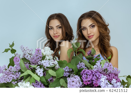 Studio fashion portrait photo of two twins women with a bouquet of spring flowers 62421512