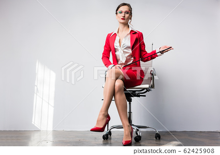 Arrogant businesswoman with a whip in her chair 62425908