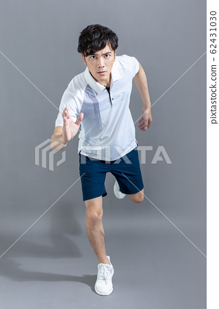 portrait of  fitness young man running on the gray 62431030