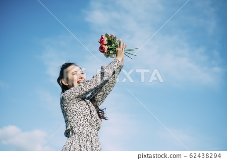 Portrait of a woman holding a flower 62438294