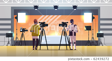 robotic operator with cameraman using video camera on tripod robot vs human standing together broadcasting artificial intelligence technology concept news studio interior full length horizontal 62439272