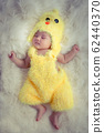 Baby portrait  :Happy sleeping Asian baby wearing yellow rooster for Chinese sign of zodiac year dress suit sleep on furry soft fabric with sweet daydream. Portrait of first month Asia baby model. 62440370