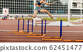 female athlete run 400 meters hurdles 62451477