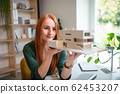 Architect with model of a house sitting at the desk indoors in office. 62453207