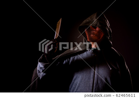 Scary killer in mask holding knife 62465611
