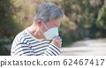 elder coughs and wears mask 62467417